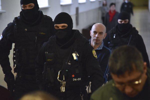 Obžalovaný Richard B. prezývaný Kofola prichádza v putách na pojednávanie v prípade vraždy zakladateľa bratislavskej skupiny sýkorovcov Miroslava Sýkoru.