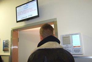 Automat na stene vydáva poradové lístky. Monitor nad dverami ambulancie ukazuje aktuálne čísla.