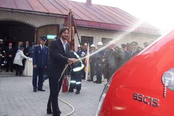 Minister Kaliňák pokrstil nové auto vodou z ručnej hasičskej striekačky.