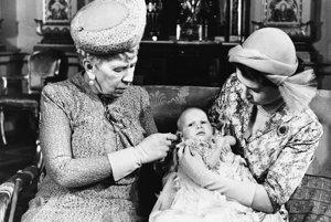 Na archívnej snímke z 21. októbra 1950 kráľovná Mary (vľavo) sa dotýka svojej pravnučky, princeznej Anny, ktorú drží v náručí jej matka princezná Alžbeta počas krstu princeznej Anny v  Buckinghamskom paláci v Londýne.