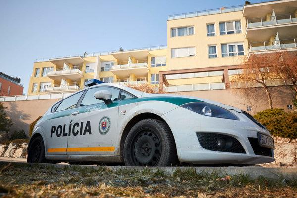 Policajné auto a komplex budov na Tupého ulici, kde prebieha policajná razia v prípade Bašternák.