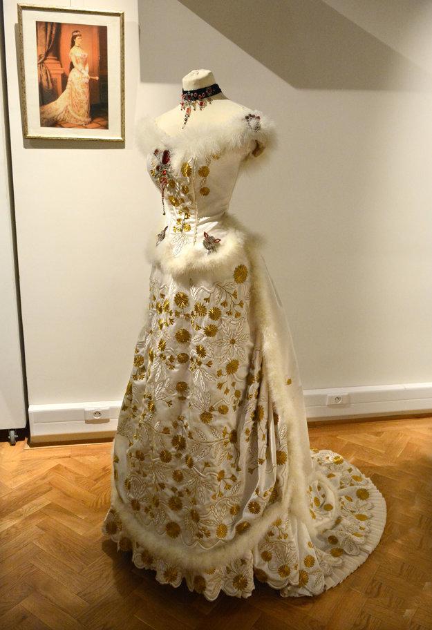 Morbídny dar. Bielo-zlaté šaty si dala Sissi ušiť špeciálne k červenej kolekcii šperkov, ktoré dostala od svojej svokry. Tie dlho ležali nevyužité v klenotnici, pretože pôvodne patrili Márii Antoinette a Sissi musela prekonať nepríjemný pocit.