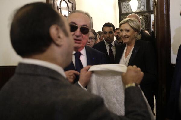 Muftiho asistent ponúka Le Penovej šatku na prikrytie hlavy.