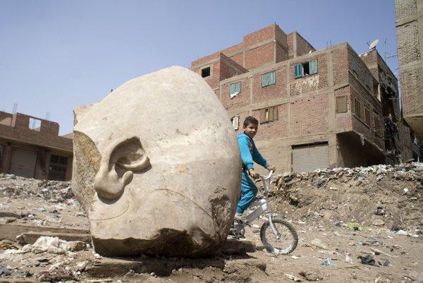 Chlapec sa bicykluje okolo väčšieho úlomku sochy.