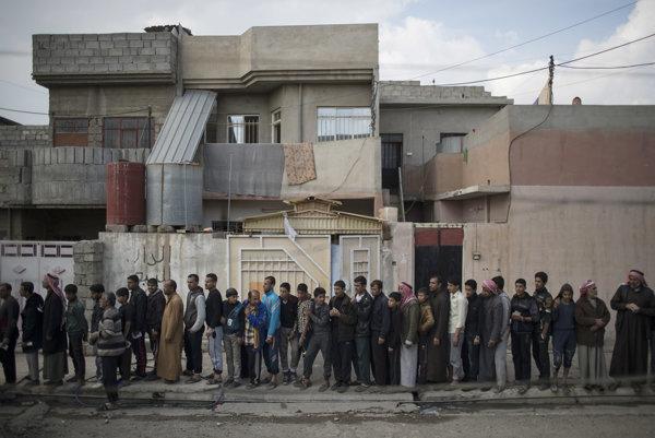 Mósulčania z oslobodenej štvrte čakajú na prídel jedla.