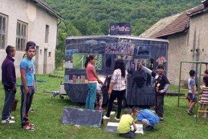 Z druhej strany karavanu je veľká tabuľa, na ktorú deti kreslia príbehy. Na tejto fotografii deti z Paškovej.