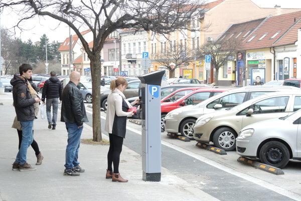 Ľudia stoja v rade na parkovacie lístky.
