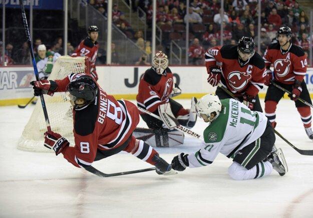 Pred bránou New Jersey padá hráč Devils Beau Bennett (vľavo) po súboji s Curtisom McKenziem z Dallasu.