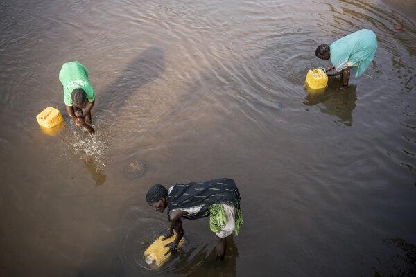 Ženy naberajú vodu z rieky do bandasiek v dedine Torit v Južnom Sudáne.
