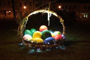 Košík s obrovskými kraslicami je v noci osvetlený.