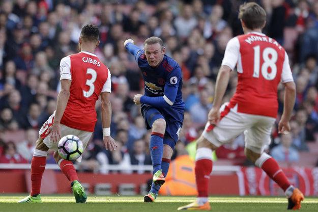 Wayne Rooney (v strede) strieľa loptu na bránu Arsenalu.