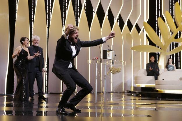 Ruben Östlund vyzýva publikum v Cannes,, aby sa uvoľnilo a zvriesklo ako zviera. V pozadí herečka Juliette Binoche a španielsky režisér Pedro Almodóvar.