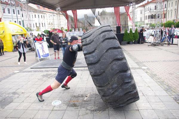 Namáhavé prevracanie veľkej a ťažkej pneumatiky na bystrickom námestí.