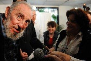 Zhrbený Fidel Castro hovorí vo volebnej miestnosti s novinármi.