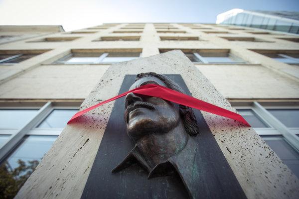 Červenou stuhou zahalené oči sochy Jána Langoša.