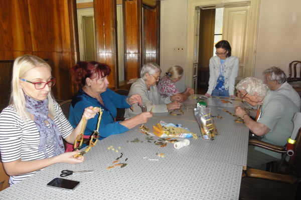 Skupina senioriek tvorí šperky zcestovín. Vľavo Jarmila Hlinková, v pozadí v strede Dominika Juricová.