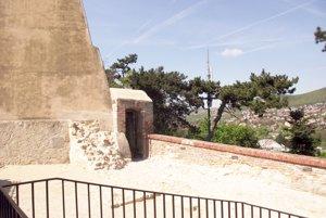 Pohľad na bránku, za ktorou je lesopark, zo strechy hradnej kaviarne.