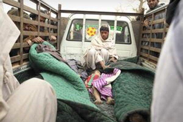 Afganec sedí pri obetiach útoku vojaka.