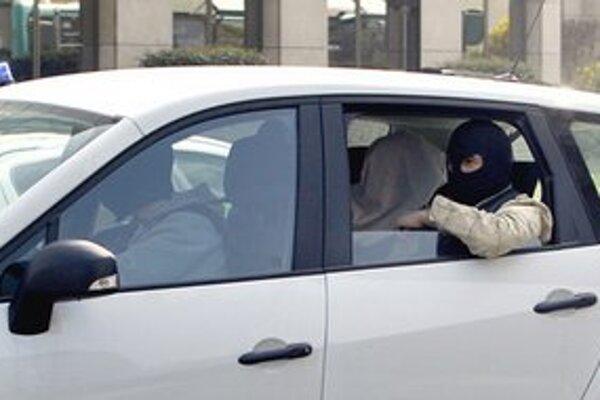 Policajti prevážajú strelcovho brata so zakrytou hlavou na výsluch.