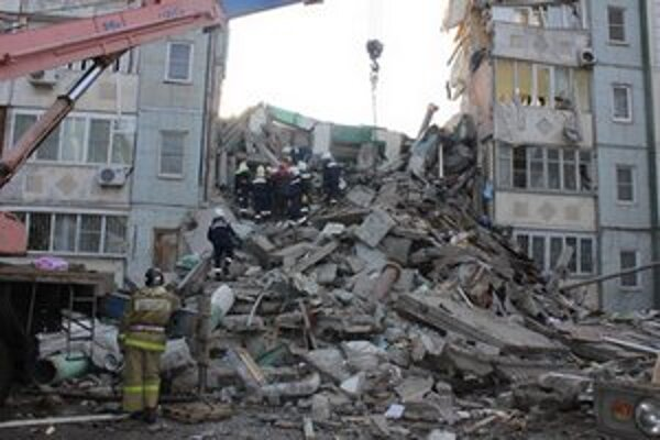 Záchranári prehľadávajú trosky zrútenej bytovky po výbuchu plynu.