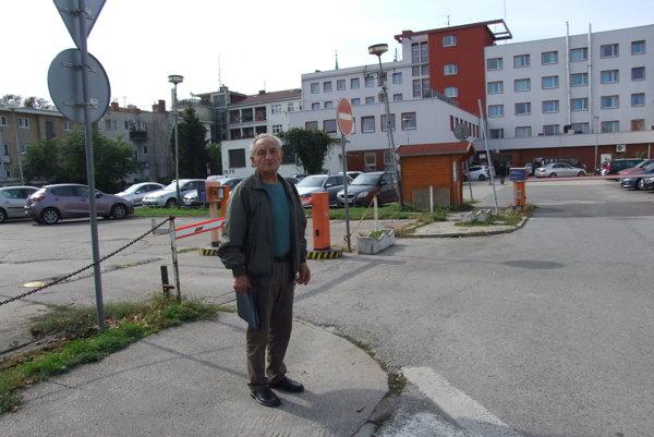 Ladislav Zvalo pred parkoviskom. Keď ho kúpil hotel, osadili rampy a zaviedli poplatok. Od júna sa zvýšil na 2 eurá za hodinu. Vľavo sú bytovky, ku ktorým sa dá dostať autom len cez parkovisko.