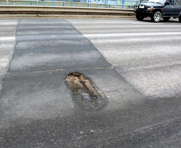 Neposlušný asfalt. Diera v ňom sa urobila opäť, hoci nedávno sa tam plátalo.