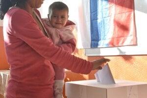 Na snímke volička vhadzuje obálku s hlasovacími lístkami do volebnej schránky počas volieb do orgánov samosprávnych krajov v rómskej osade v Trebišove.