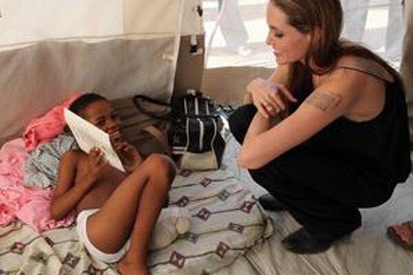 Americká herečka Angelina Jolieová včera v mene OSN prišla na Haiti. Na snímke v nemocnici hovorí s chlapcom, ktorý prišiel o nohu.