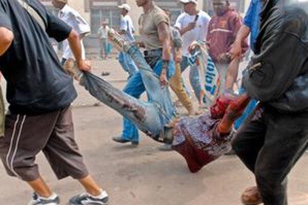 Madagaskarčania odnášajú zraneného demonštranta v Antananarivu 7. februára 2009. Krajinu sužujú už druhý mesiac masové protivládne protesty a nepokoje, ktoré si doteraz vyžiadali vyše 130 obetí na životoch.