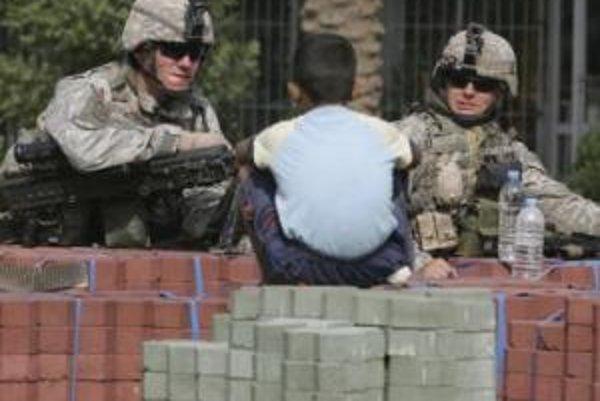 Chlapec sleduje amerických vojakov na kontrolnom bode v Bagdade.