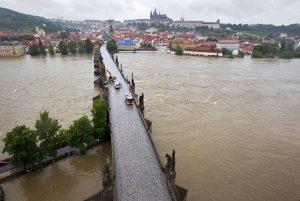 Karlov most v Prahe strážia pre valiacu sa vodu policajti, hasiči a tiež bager. Jeho dlhé rameno odstraňuje z pilierov naplavené kusy stromov, konárov aj záhradných domčekov. (3. júna 2013) Autor: Michal Růžička, MAFRA