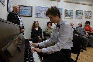 Na vernisáži. Na klavíri hrá žiar Súkromnej ZUŠ Maše Haľamovej Andrej Piecka.