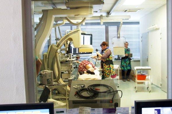 Pacientka po zákroku, pohľad cez sklo.