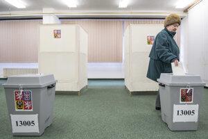 Volička vhadzuje svoj hlas do volebnej urny v Prahe.