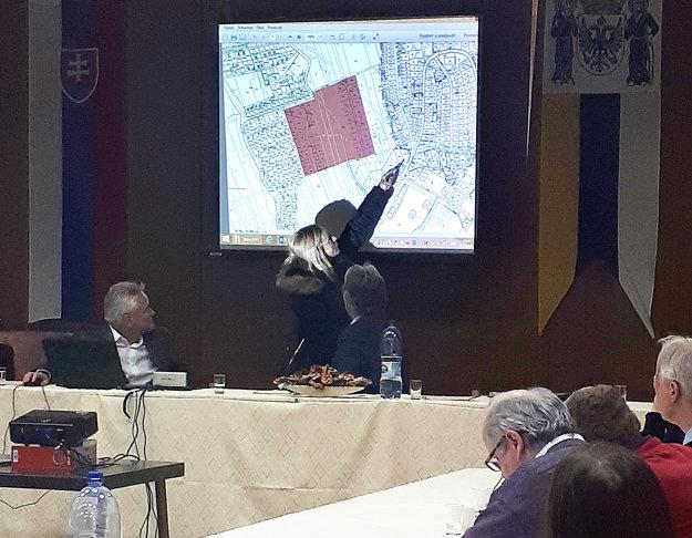 Jedna zvlastníčok ukazuje na mape, ktorú časť plánovanej cesty predajú mestu po eure.