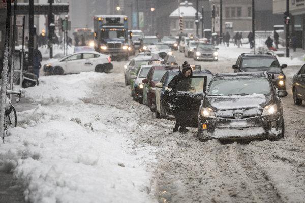Spomalená premávka na zasneženej ceste počas hustého sneženia v Chicagu.