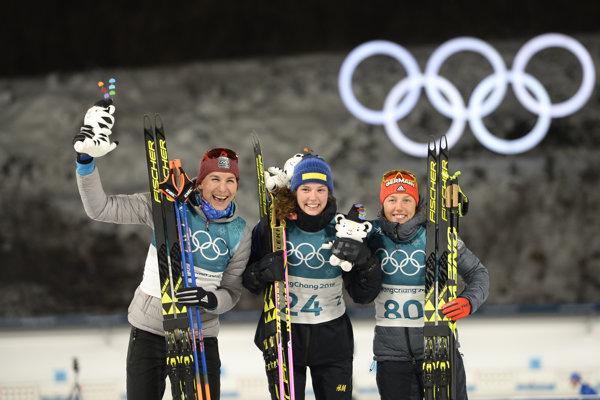 Pred objektívmi pózujú tri najlepšie biatlonistky z vytrvalostných pretekov na 15 kilometrov - zľava strieborná Anastasia Kuzminová, zlatá Švédka Hanna Hanna Öbergová a bronzová Nemka Laura Dahlmeierová.