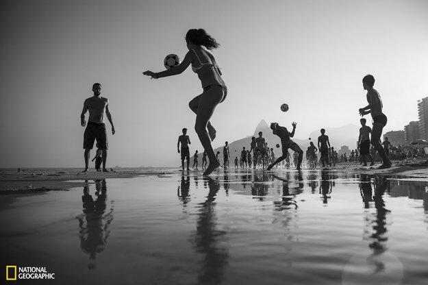 Ľudia na pláži Ipanema v Rio de Janeiro sa hrajú miestnu loptovú hru.