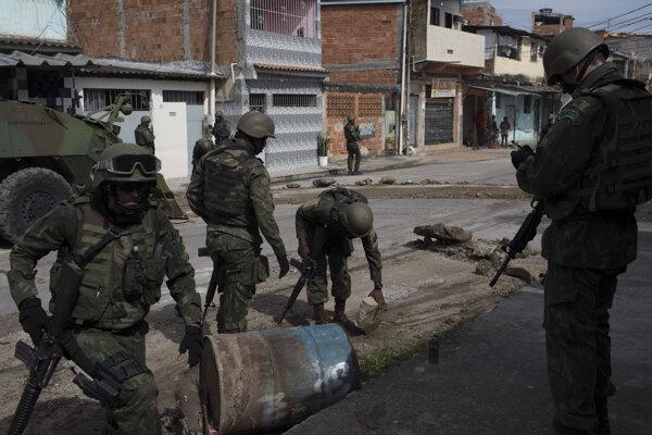Príslušníci brazílskej námornej pechoty rozoberajú barikádu v jednej z ulíc Ria de janeira.