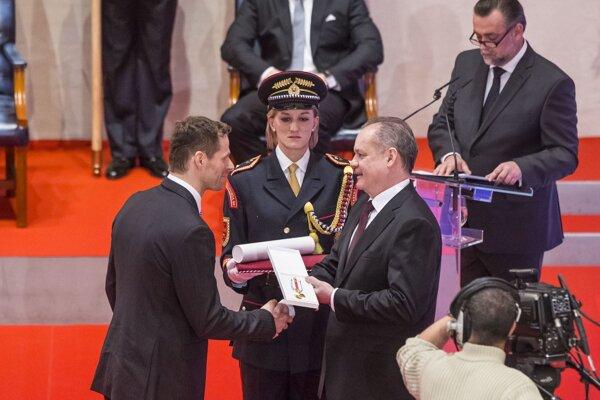 Michal Handzuš  pri preberaní ocenenia z rúk prezidenta.