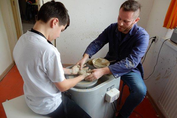 Na snímke chlapec v špeciálnej základnej škole pre deti s autizmom v obci Klokočov v Michalovskom okrese pri hrnčiarskom kruhu spolu s učiteľom.