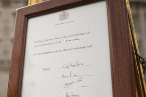Oznam o narodení nového Kráľovského dieťaťa postavený na stojane pred Buckinghamským palácom.