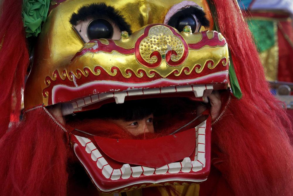 Tanečník s maskou leva vykúka z tlamy. TASR/AP