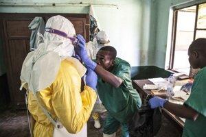 Zdravotníci sa chránia pred nákazou v ohnisku výskytu eboly.
