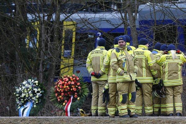 Záchranári stoja vedľa vencov na mieste zrážky dvoch vlakov v nemeckom Bad Aiblingu.