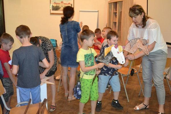 Učiteľka Bibiána Bilšáková (na snímke) a historička Zuzana Koščová pomáhali deťom s výrobou koníkov.