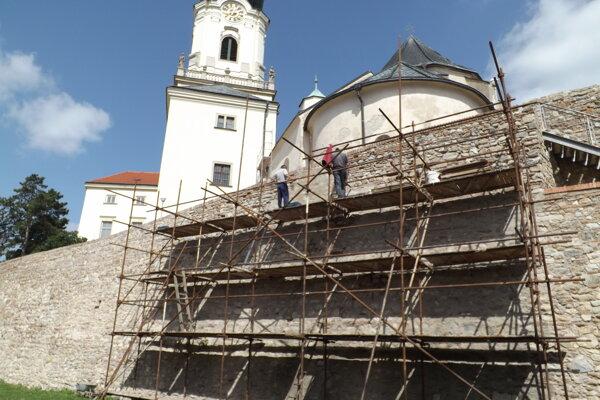 V hradnej priekope je lešenie. Zo stien odstraňujú cementové nánosy.