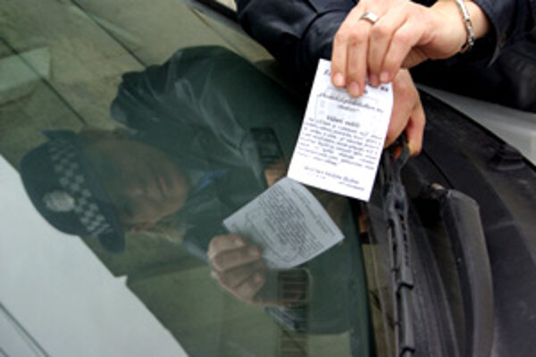Mestská policajtka umiestňuje za stierač leták s heslom: Chodník je predovšetkým pre chodcov.