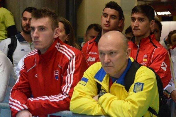 Miroslav Škvarek (vľavo v červenej mikine) pozorne sleduje zápasy ostatných karatistov.