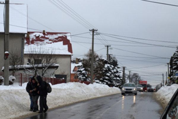 Chodníky sú zasypané snehom, ľudia chodia po frekventovanej ceste.